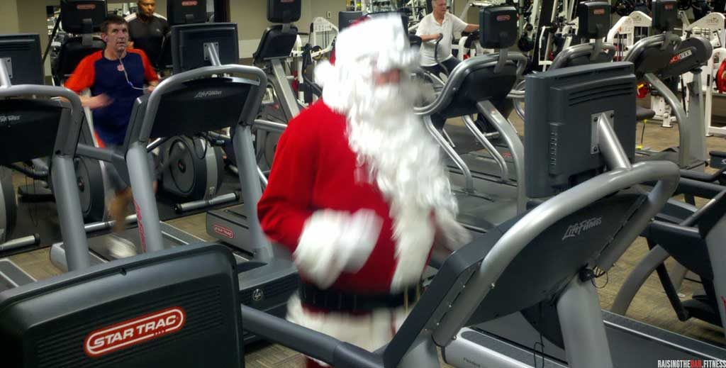 Man dressed as father Christmas in the gym on a treadmill