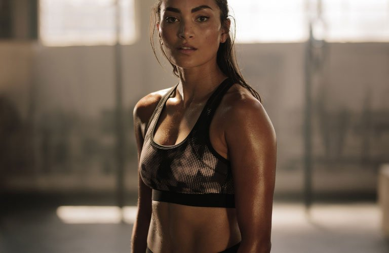 Fit woman glistening in sweat looking at the camera