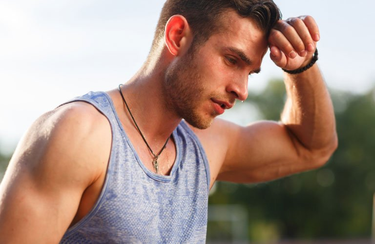 Fit man outside rubbing sweat off his brow