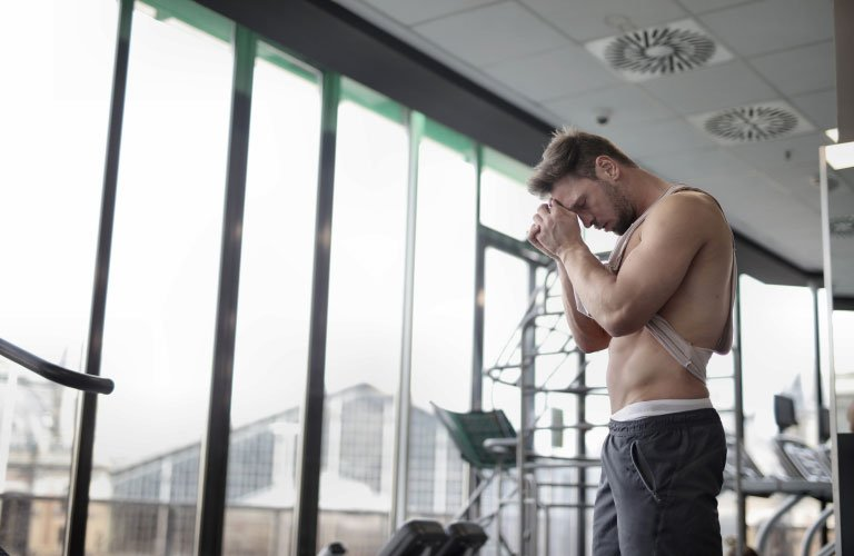 Fit man in gym rubbing the sweat off his brow with training shirt
