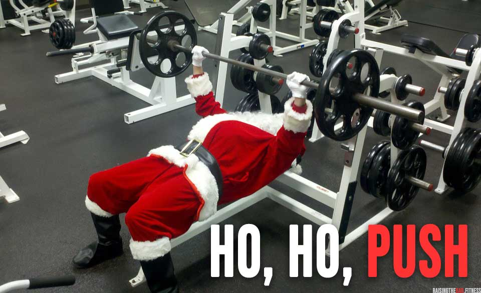 """A man dressed as father Christmas in the gym doing a bench press and the words """"ho, ho, push"""""""