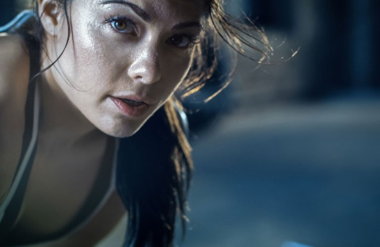 Fit woman after workout looking at the camera with sweat glistening