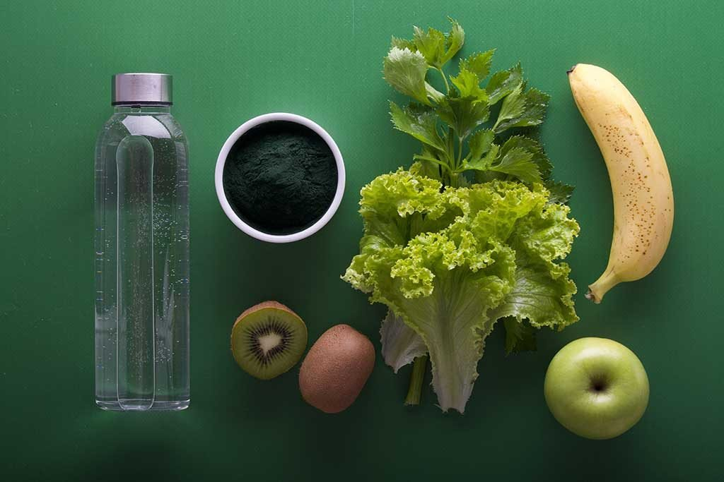 Ingredients for a green smoothie laid out on a green background includes banana, apples, kiwi, lettuce and spirulina