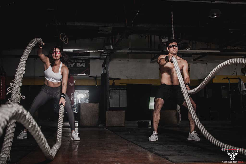 A man and a woman side by side in the gym both using battle ropes
