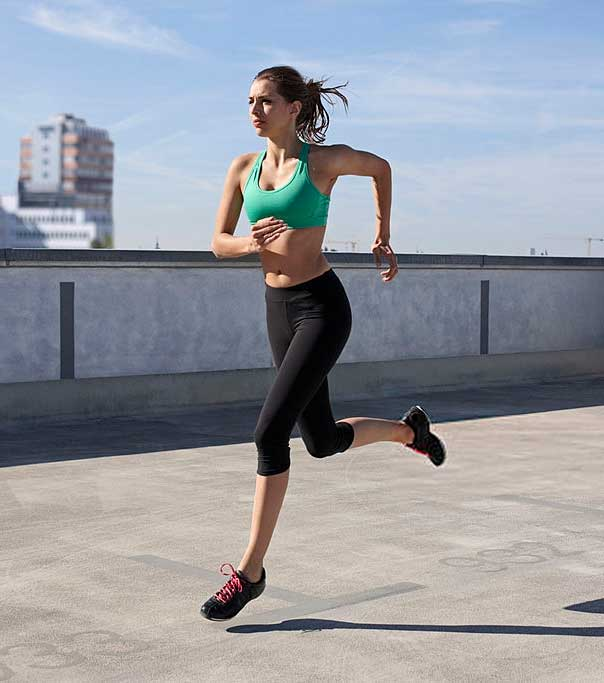 Woman running outside with blue sky and city scape in the background